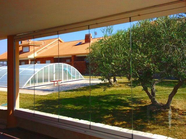 cerramientos-de-terraza-cortina-de-cristal-jardín-con-piscina